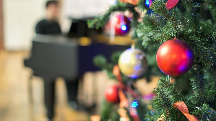 Christmas tree with teacher playing festive music for Christmas play