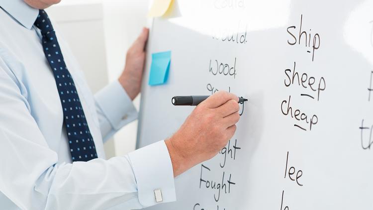 Image of teacher writing spellings on a whiteboard for KS1 and KS2 pupils