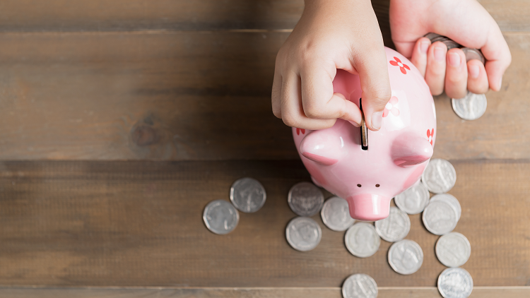 Child saving using a piggy bank representing primary maths lessons about money, coins, notes, pounds and pence