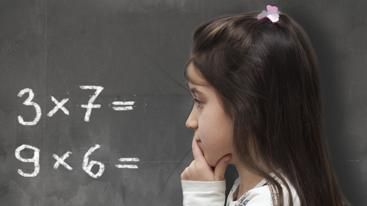 Young girl thinking about multiplication sums on a blackboard