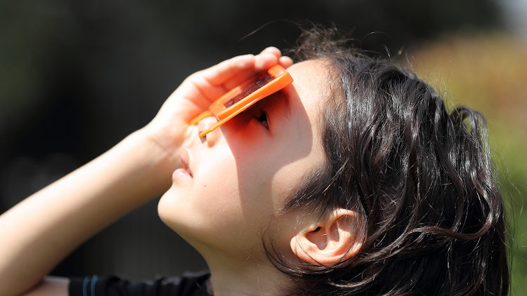 A girl looking up wearing solar eclipse glasses