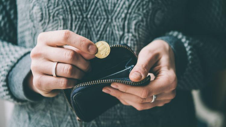 Someone puts a coin into a purse