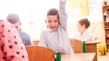 boy raising hand to answer a question to a fun game in a classroom