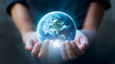 person holding the world in their hand to signify climate change resources