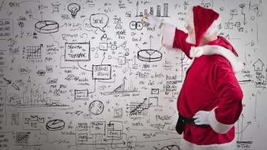 Father Christmas completing secondary maths activities on a classroom whiteboard