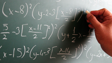 Teacher writing algebra and maths symbols on blackboard to test students
