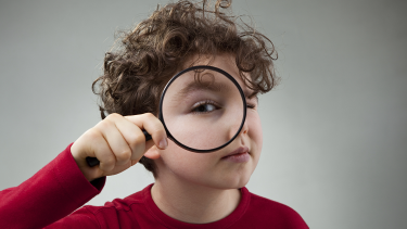 Child holding a magnifying glass solving a mystery/looking at something closer