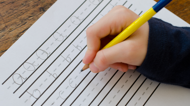 Image of child writing letters of the alphabet to show primary english handwriting and letter formation