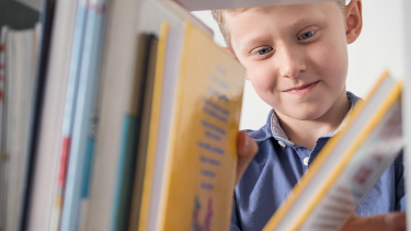 Primary pupil looking through library books reflecting the development of a reading culture