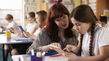Teacher helping child ahead of KS1 tests and KS2 Sats, in English and maths