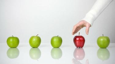A teacher selects an apple
