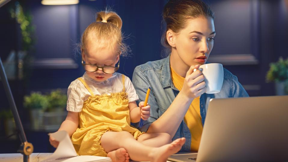 Mother, sitting at computer, with small child helping her with her work