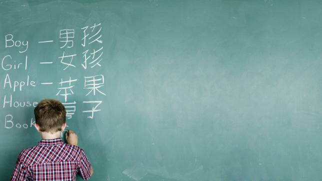 Boy at blackboard, learning Mandarin