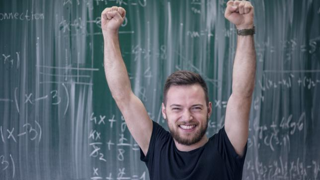 Teacher raising hand in cheer, in front of blackboard
