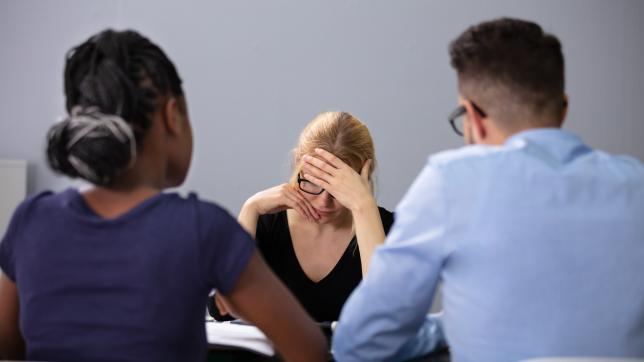 Woman looks upset in meeting; two managers sit opposite her