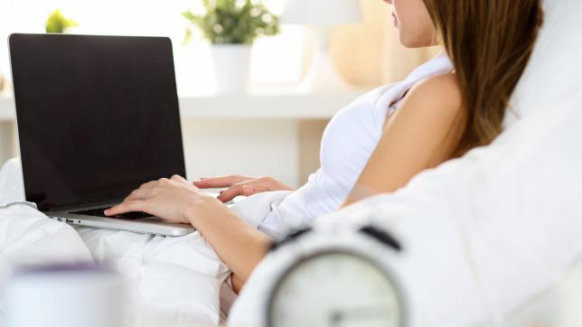 Woman on computer, in hospital bed