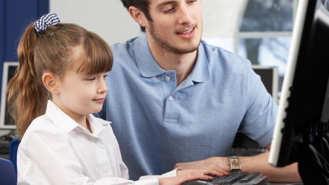 Learning support assistant sits at computer with pupil