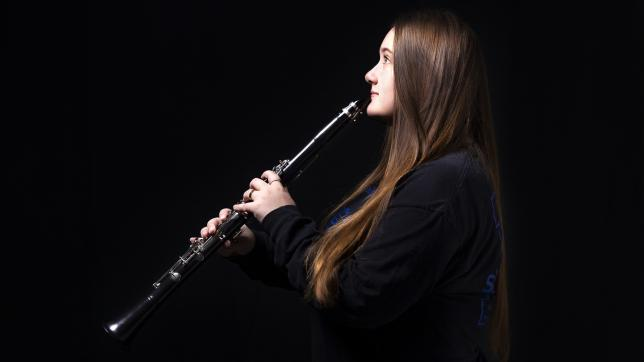 Teenage girl plays the clarinet, against dark background