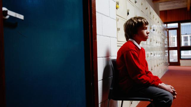 child sitting in corridor
