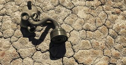 Gas mask on cracked mud