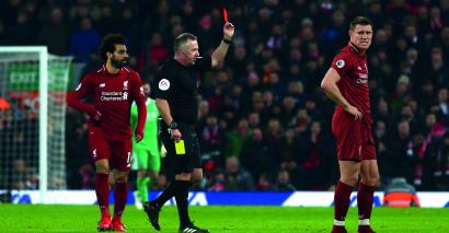 Liverpool footballer James Milner receives a red card from Jon Moss, who used to teach him at school