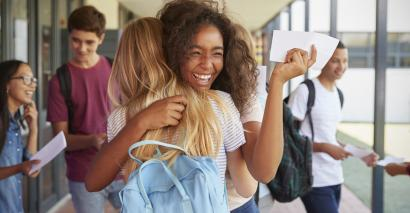 Two girls, hugging in school corridor