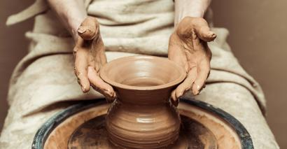 Potter turning pot on wheel