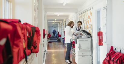 Teachers using photocopier in school corridor