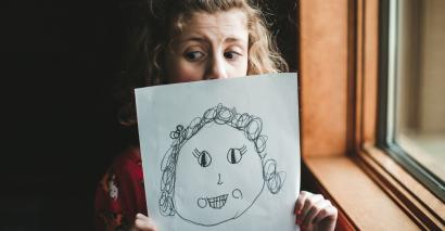 Wellbeing: worried looking girl holding drawing of a girl