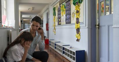 A teacher comforts an upset pupil in an otherwise empty school corridor