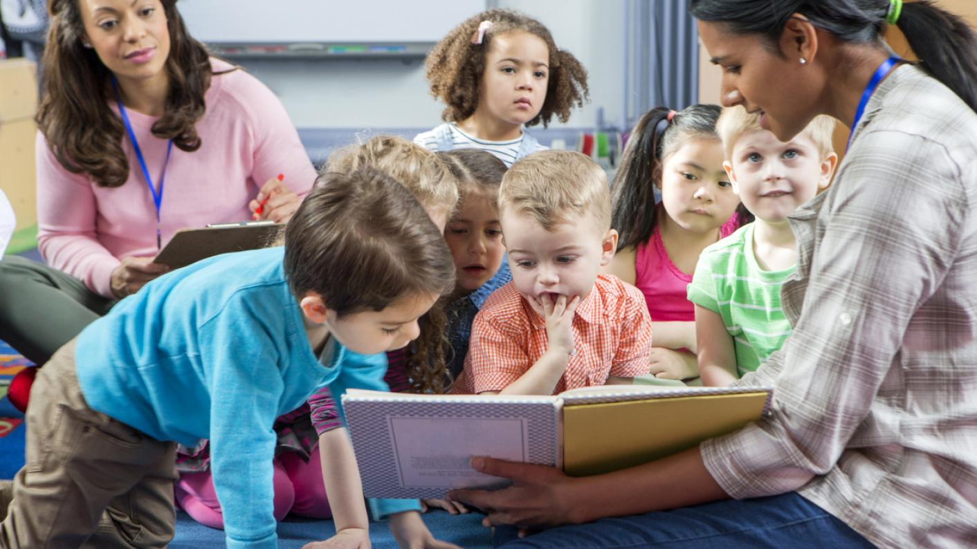 Teacher reading out loud to early-years class