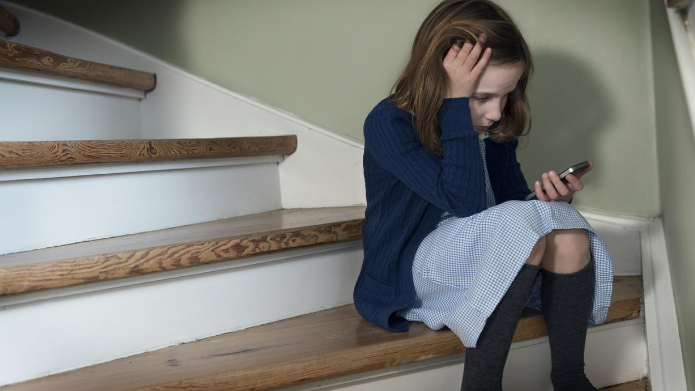 Sad-looking schoolgirl sits on stairs, with phone