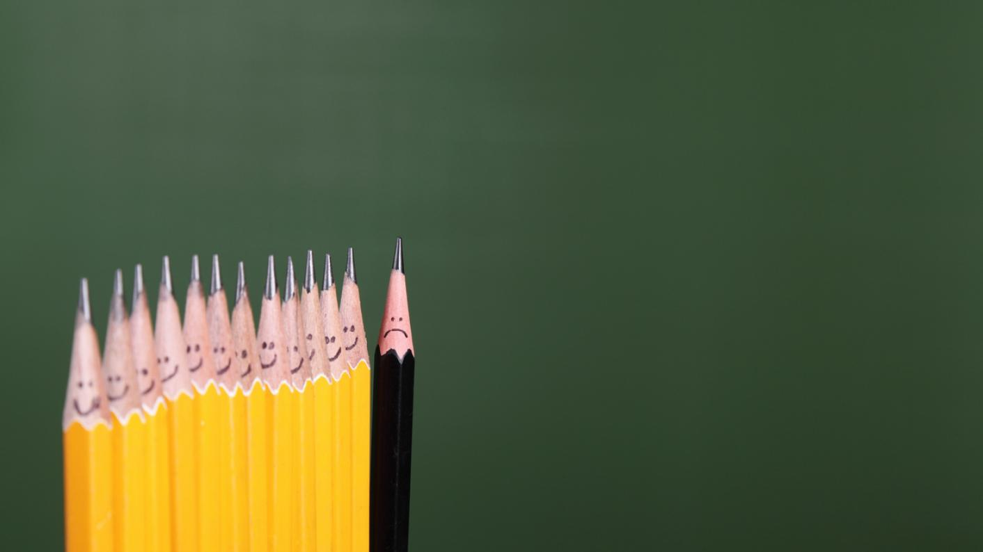 A row of smiling yellow pencil, and one black pencil, looking unhappy
